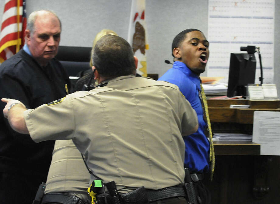 In this photo taken on Feb. 27, 2015, Kamron T. Taylor, right, is removed from a Kankakee County courtroom in Kankakee, Ill., by a bailiff and two sheriff's deputies, after struggling with the deputies and yelling at the crowd in the gallery after being found guilty of murder. Early Wednesday morning, April 1, 2015. Taylor escaped from the Jerome Combs Detention Center in Kankakee after overpowering a guard and taking his keys, uniform and SUV. (AP Photo/The Daily Journal, Mike Voss)