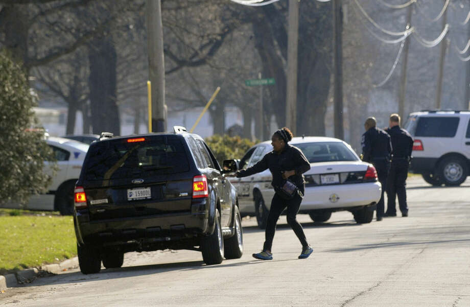 A woman rushes to her car in Kankakee, Ill., Wednesday, April 1, 2015, after being told by police that officers were searching in the area for prison escapee Kamron T. Taylor. Authorities say Taylor, a convicted murderer who escaped from the Jerome Combs Detention Center in Kankakee earlier in the day after beating a guard into unconsciousness, taking his keys and uniform and speeding off in his SUV, may be traveling with a 15-year-old girl. (AP Photo/The Daily Journal, Mike Voss)