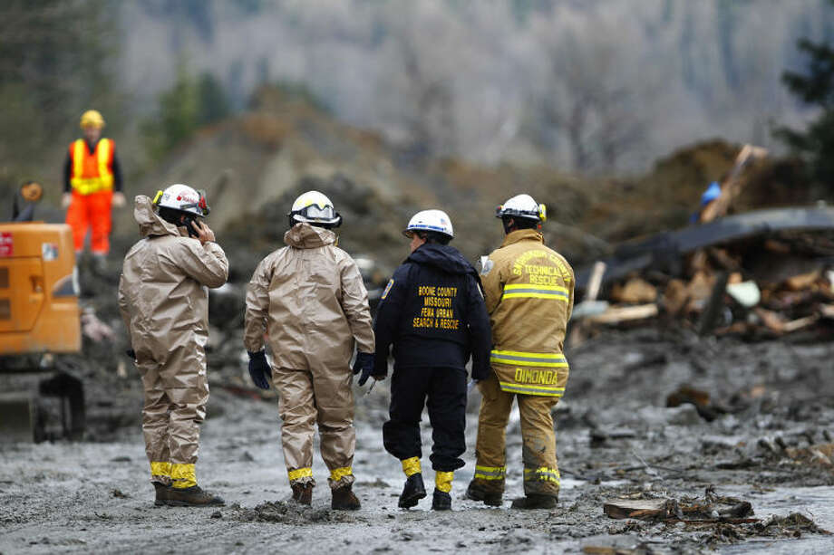 Rescue workers and work crews toil at the western edge of the mudslide where it covers Highway 530 Wednesday morning, March 26, 2013, east of Oso, Wash. Search crews using dogs, bulldozers and their bare hands kept slogging through the mess of broken wood and mud. (AP Photo/The Herald, Mark Mulligan) Photo taken 20140326