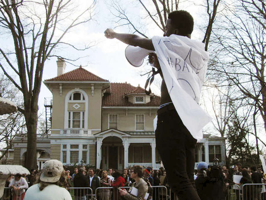 In this Tuesday March 31, 2015 photo, Ohio University senior Ryant Taylor fires up the crowd gathered in front of the president's former residence during a campus rally to protest the university moving President Roderick McDavis to a home off campus. McDavis and his wife relocated last month because of a bat infestation at the century-old house on campus. (AP Photo/Mitch Stacy)