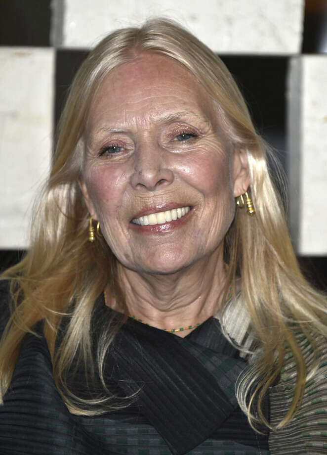 """FILE - Joni Mitchell arrives to the Hammer Museum's """"Gala In The Garden"""" in this Saturday, Oct. 11, 2014 file photo taken in Los Angeles. Mitchell was hospitalized in Los Angeles on Tuesday, March 31, 2015 according to the Twitter account and website of the folk singer and Rock and Roll Hall of Famer, but details on her condition have not been released. (Photo by John Shearer/Invision/AP, File)"""