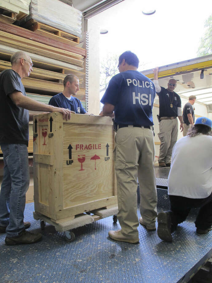 Honolulu Museum of Art workers and agents from Homeland Security Investigations load a crate into a truck outside the museum on Wednesday, April 1, 2015, in Honolulu. The museum on Wednesday handed over seven rare artifacts that it acquired without museum officials realizing they were ill-gotten items, after an international investigation into antiquities looted from India and smuggled into the United States lead authorities to the museum. (AP Photo/Jennifer Sinco Kelleher)