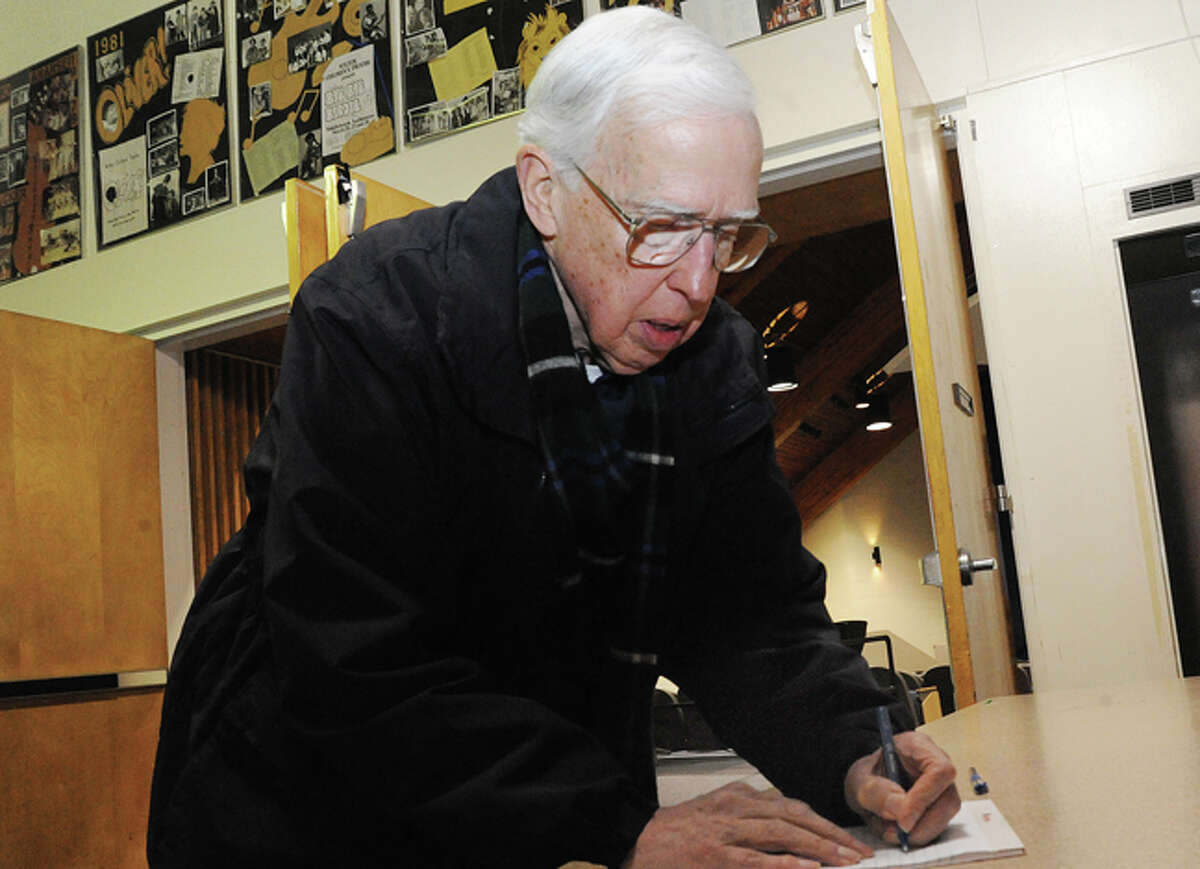 Wilton resident Curt Noel signs in to speak Tuesday at the Middlebrook School auditorium during the 2014-15 municipal budget meeting.