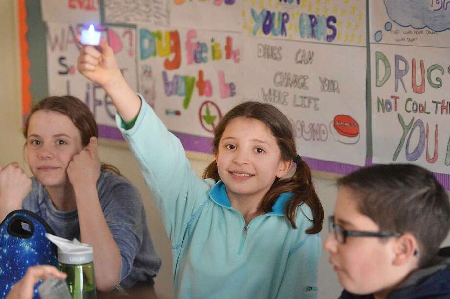 Hour Photo/Alex von Kleydorff West Rocks school 6th grader Rachel Lasky along with other students light an electronic blue colored candle to draw attenetion to World Autism Awareness Day.