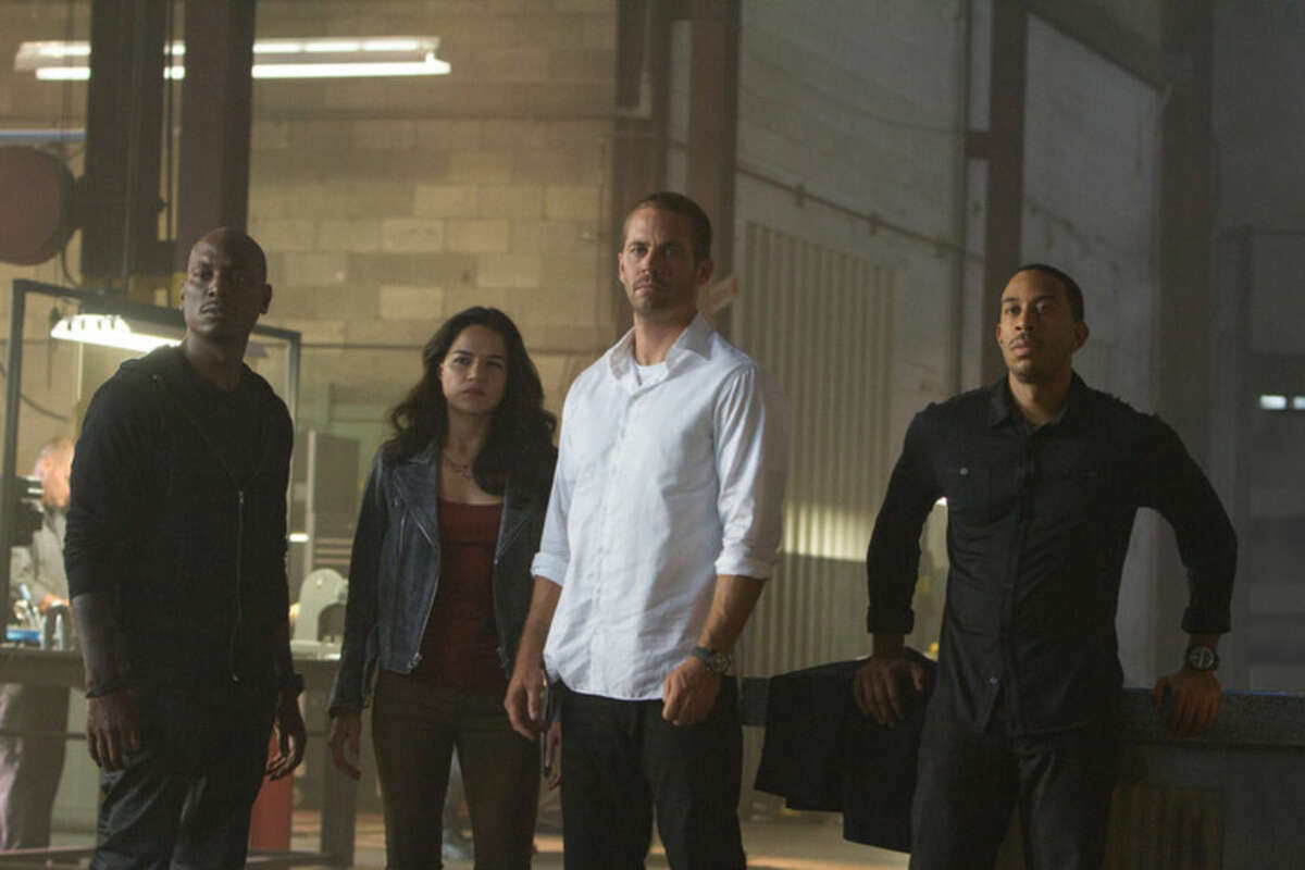 This photo provided by Universal Pictures shows, from left, Tyrese Gibson as Roman, Michelle Rodriguez as Letty, Paul Walker as Brian, and Chris Ludacris as Tej, in a scene from
