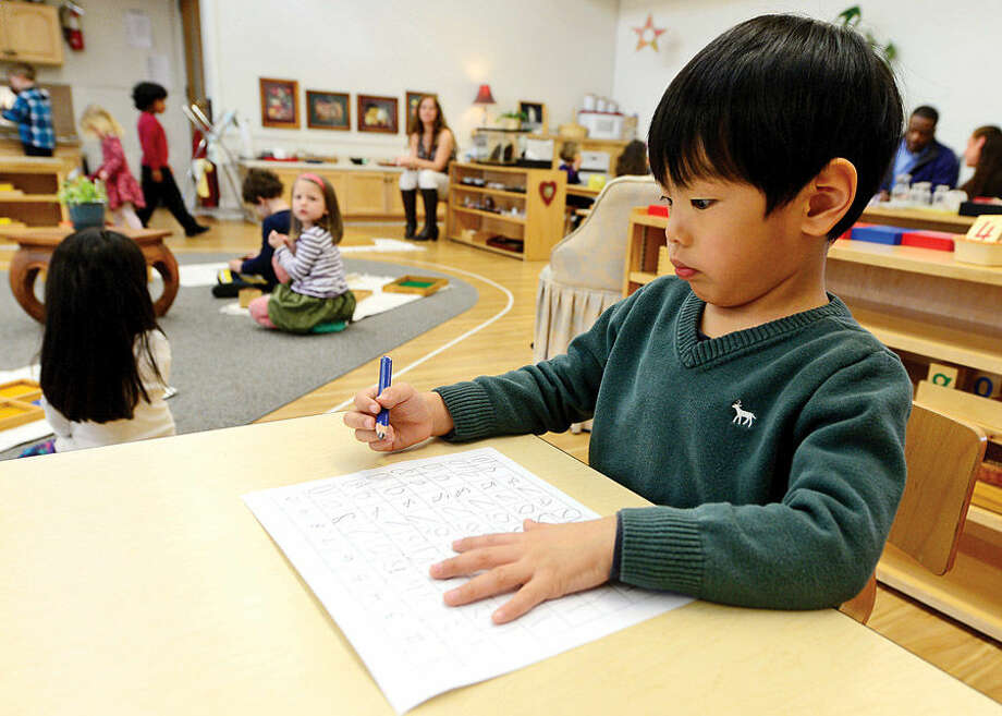 Hour photo / Erik Trautmann Students at the Montessori School in Wilton inclduing Anthony Low engage in educational activity during their time at the school Wednesday. Montessori education is an approach characterized by an emphasis on independence, freedom within limits, and respect for a child's natural psychological, physical, and social development.