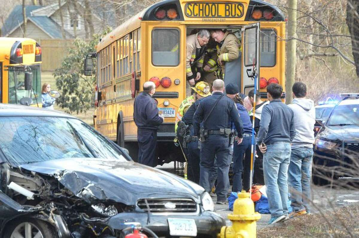 Hour Photo/Alex von Kleydorff Wilton Firefighters and Paramedics move an adult to a stretcher from the rear of a school bus at an accident scene involving multiple vehicles and a Norwalk Public School bus on the Wilton Westport line, Thursday at 3:30