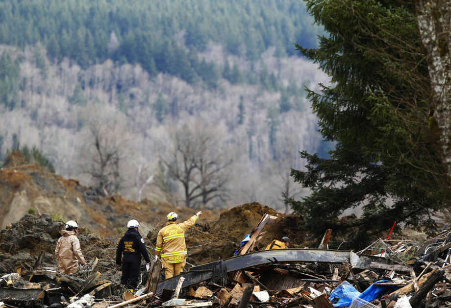 Searchers examine the area on the western edge of the mudslide where it covers Highway 530 Wednesday morning, March 26, 2014, east of Oso, Wash. The debris field is about a square mile and 30 to 40 feet deep in places, and includes quicksand-like muck, rain-slickened mud and ice. (AP Photo/The Herald, Mark Mulligan )
