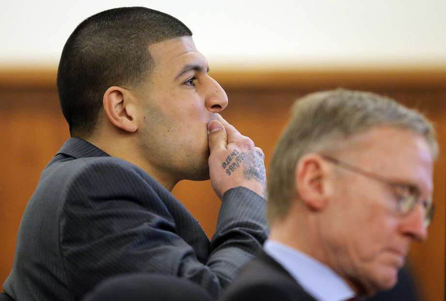 Former New England Patriots NFL football player Aaron Hernandez, left, listens alongside his attorney Charles Rankin as prosecution witness Alexander Bradley is questioned by the prosecution without the jury present during his murder trial, Wednesday, April 1, 2015, at Bristol County Superior Court in Fall River, Mass. Hernandez is accused of killing Odin Lloyd in June 2013. (AP Photo/Brian Snyder, Pool)