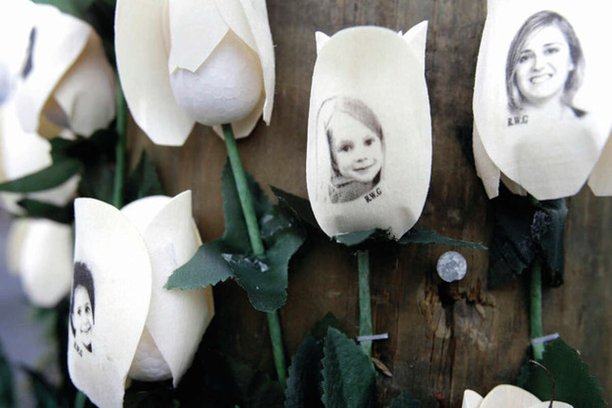 AP photo / Seth Wenig Photos showing victims of shootings at Sandy Hook Elementary School are imprinted on fake roses at a memorial in the village of Newtown Saturday.