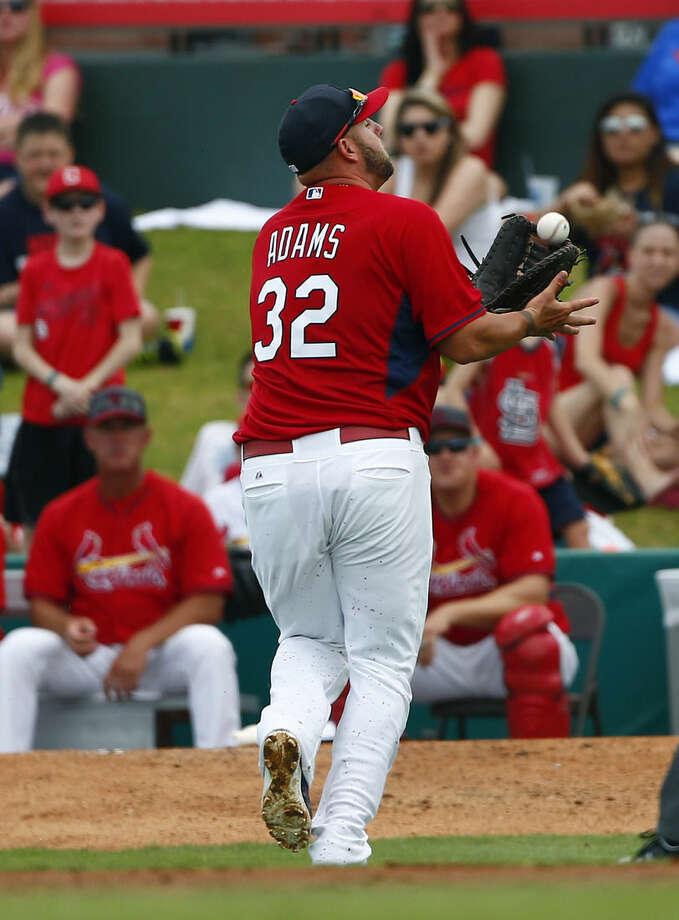 St. Louis Cardinals first baseman Matt Adams (32) makes a running catch to retire New York Mets' Michael Cuddyer in the second inning of an exhibition spring training baseball game Thursday, April 2, 2015, in Jupiter, Fla. (AP Photo/John Bazemore)