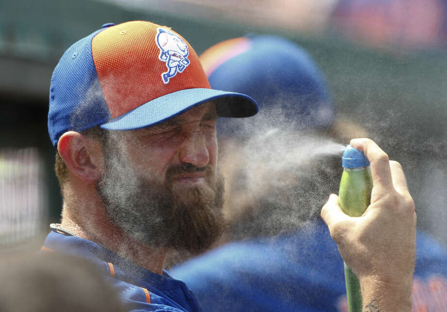 New York Mets pitcher Jonathon Niese applies sunscreen before an exhibition spring training baseball game against the St. Louis Cardinals Thursday, April 2, 2015, in Jupiter, Fla. Niese was not in the lineup and the game ended in a 0-0 tie. (AP Photo/John Bazemore)