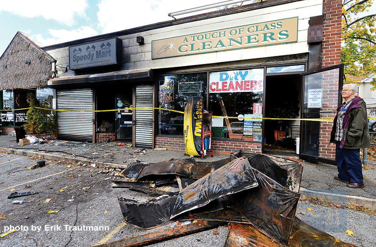 Hour photo / Erik Trautmann A business owner looks over the Ludlowe Shooping Centre in East Norwalk that was damaged by a devastating fire Thursday afternoon.