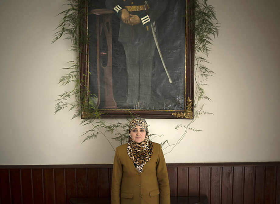 In this Wednesday, March 26, 2014 photo Afghan lawmaker Fatema Aziz from Kunduz poses under an oil painting in the parliament in Kabul, Afghanistan. When the Taliban ruled, women rarely left their home. When they did venture beyond their four walls, they wafted through crowded markets covered from head to toe in the all-encompassing burqa. While most women in conservative Afghanistan may still wear the burqa, today's Afghan woman has choices she never had before, like running for parliament. (AP Photo/Anja Niedringhaus)
