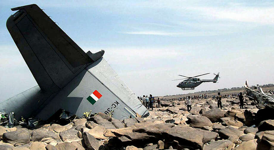 An Indian air force (IAF) helicopter hovers over the site where an IAF cargo plane crashed near Karauli village in the central Indian state of Madhya Pradesh, Friday, March 28, 2014. C-130J Hercules plane inducted into service just last year crashed during a training mission Friday, killing all five crew members in the latest in a series of accidents that have hit the Indian armed forces. (AP Photo)