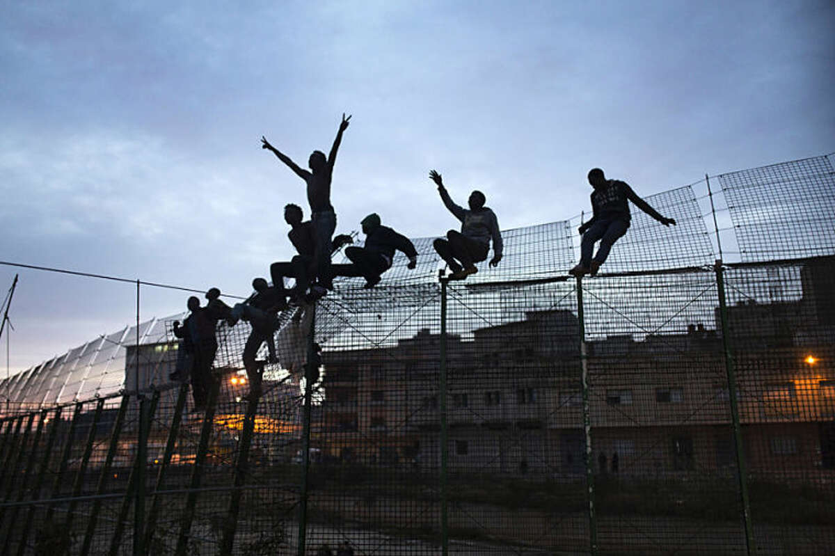 Sub-Saharan migrants climb over a metallic fence that divides Morocco and the Spanish enclave of Melilla on Friday March 28, 2014. Officials said several hundred African migrants tried to cross barbed-wire border fences to enter the Spanish enclave of Melilla from Morocco but most were turned back by security forces from both sides. An Interior Ministry spokesman in Melilla said the migrants attempted to scale the fences several times early Friday and a handful managed to get across. Thousands of migrants seeking a better life in Europe are living illegally in Morocco, hoping they can enter Melilla and Spain's other north African coastal enclave, Ceuta. (AP Photo/Santi Palacios)
