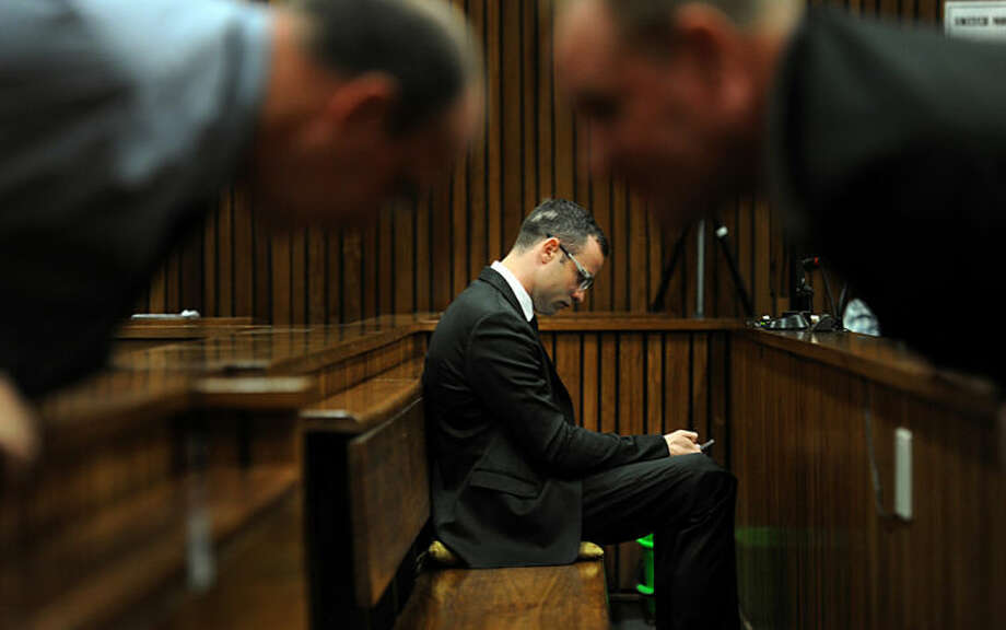 Oscar Pistorius sits in the dock inside court in Pretoria, South Africa, Friday, March 28, 2014, as members of his defense team, foreground, talk over benches. The murder trial of Oscar Pistorius has been delayed until April 7 because one of the legal experts who will assist the judge in reaching a verdict is sick, abruptly ending expectations Friday that the double-amputee athlete was about to testify on his fatal shooting of girlfriend Reeva Steenkamp. (AP Photo/Werner Beukes, Pool)