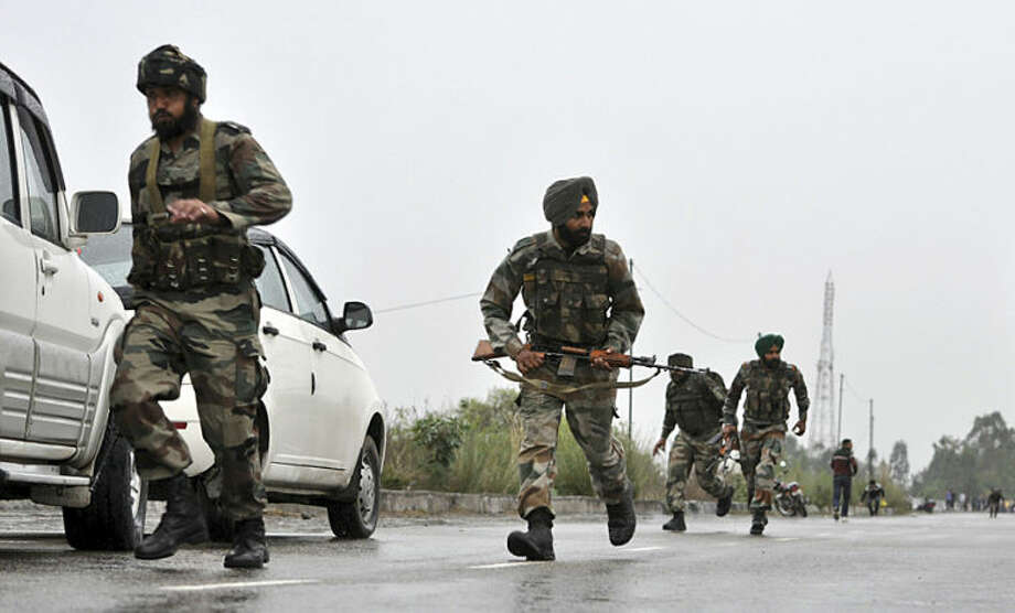 Indian army soldiers run to take position on the Jammu-Pathankot highway during a gunbattle in Kathua district, in Indian-controlled Kashmir, Friday, March 28, 2014. Gunmen disguised as Indian soldiers opened fire on a car Friday, killing a passenger and triggering a firefight with army troops, authorities said. The assailants sped away in the car, but army troops intercepted them about 30 kilometers (20 miles) away, the officer said. The ensuing gunbattle lasted at least three hours. (AP Photo/Channi Anand)