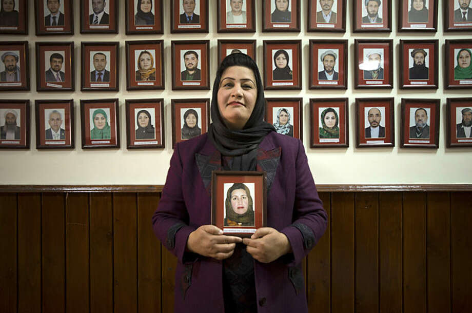 In this Wednesday, March 26, 2014 photo, Afghan lawmaker Samia Azizi Sadat from Parwan holds her picture which hangs on the wall among Afghanistan's 249 parliamentarians in the parliament in Kabul, Afghanistan. In the last elections in 2010, 69 women won seats in Afghanistan's 249-seat parliament. The next parliamentary vote will be held in 2015, but first are the April 5 presidential and provincial council elections. (AP Photo/Anja Niedringhaus)