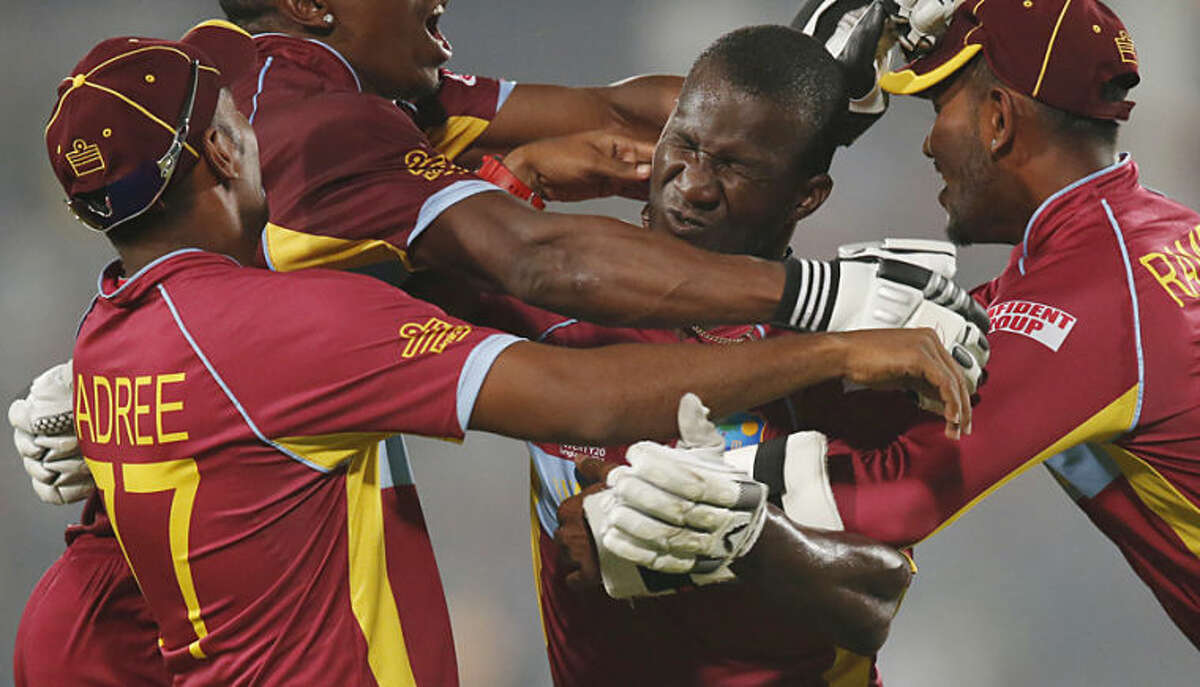 West Indies' players pounce on captain Darren Sammy, second right, to celebrate their win over Australia in the ICC Twenty20 Cricket World Cup match in Dhaka, Bangladesh, Friday, March 28, 2014. West Indies won the match by six wickets. (AP Photo/Aijaz Rahi)