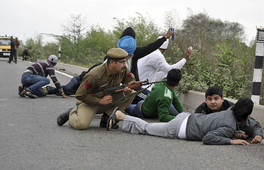 Indian security officers and civilians take cover on the Jammu-Pathankot highway during a gunbattle in Kathua district, in Indian-controlled Kashmir, Friday, March 28, 2014. Gunmen disguised as Indian soldiers opened fire on a car Friday, killing a passenger and triggering a firefight with army troops, authorities said. The assailants sped away in the car, but army troops intercepted them about 30 kilometers (20 miles) away, the officer said. The ensuing gunbattle lasted at least three hours. (AP Photo/Channi Anand)