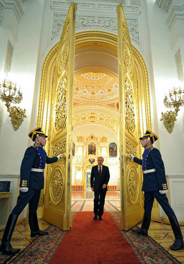 Russian President Vladimir Putin enters a hall to attend the presentation ceremony of the top military brass in the Kremlin in Moscow, Russia, Friday, March 28, 2014. Russia's president says Ukraine could regain some arms and equipment of military units in Crimea that did not switch their loyalty to Russia. (AP Photo/RIA-Novosti, Alexei Druzhinin, Presidential Press Service)