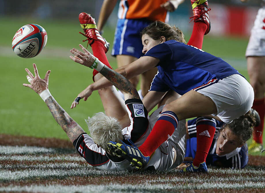 Canada's Jennifer Kish, left on the ground, is tackled by France's Jade Le Pesq, right, during the final match of Women's Invitational Cup at the Hong Kong Sevens rugby tournament in Hong Kong, Friday, March 28, 2014. Canada won 24-0. (AP Photo/ Kin Cheung)