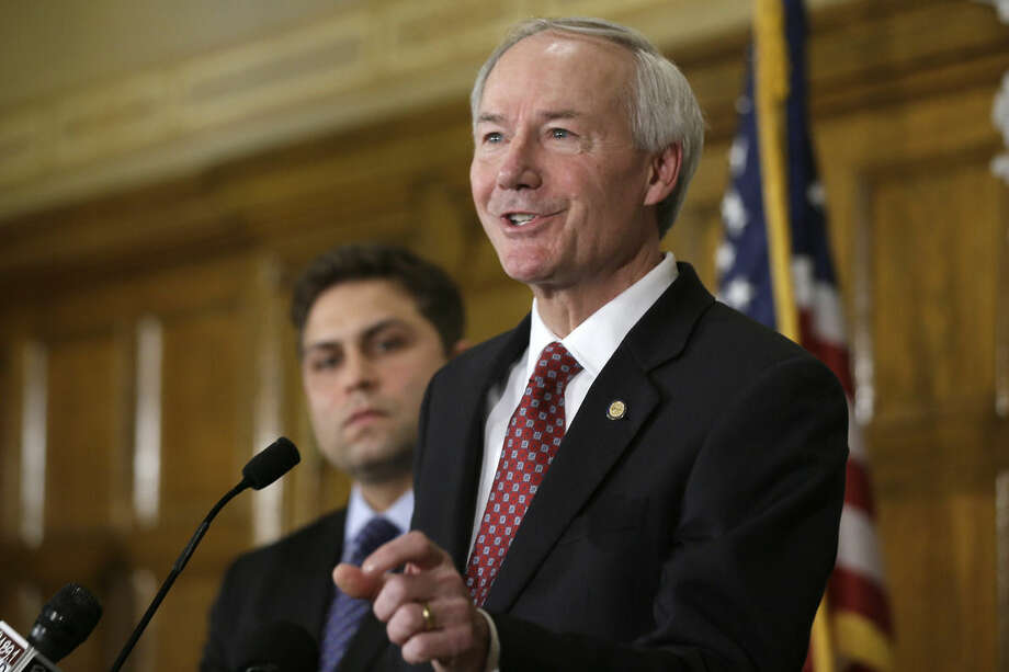 Arkansas Gov. Asa Hutchinson, right, answers reporters' questions as Sen. Jonathan Dismang, R-Beebe, lisens at the state Capitol in Little Rock, Ark., Wednesday, April 1, 2015. Hutchinson on Wednesday called for changes to the state's religious objection measure facing a backlash from businesses and gay rights groups, saying it wasn't intended to sanction discrimination based on sexual orientation. (AP Photo/Danny Johnston)