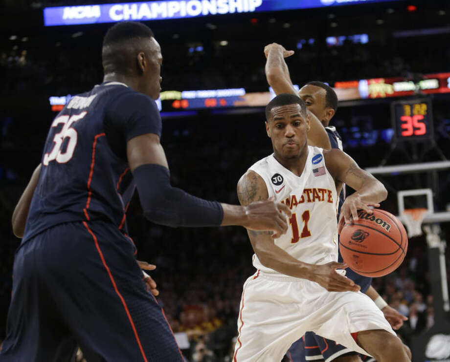 Iowa State's Monte Morris, right, moves the ball around Connecticut's Amida Brimah, left, during the first half in a regional semifinal of the NCAA men's college basketball tournament Friday, March 28, 2014, in New York. (AP Photo/Frank Franklin II)