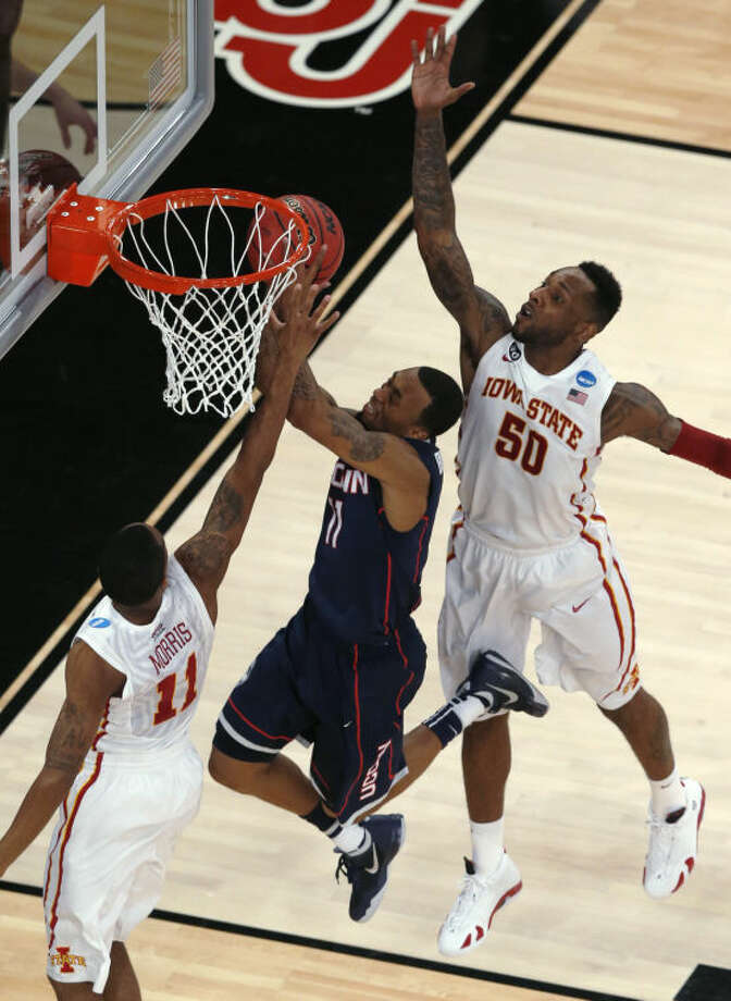 Iowa State's DeAndre Kane, right, reaches to block a shot by Connecticut's Ryan Boatright as Iowa State's Monte Morris approaches during the first half in a regional semifinal of the NCAA men's college basketball tournament Friday, March 28, 2014, in New York. (AP Photo/Julio Cortez)