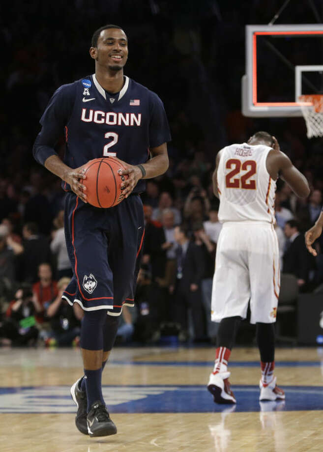 Connecticut's DeAndre Daniels walks off the court past Iowa State's Dustin Hogue after Connecticut defeated Iowa State 81-76 in a regional semifinal of the NCAA men's college basketball tournament Friday, March 28, 2014, in New York. (AP Photo/Frank Franklin II)