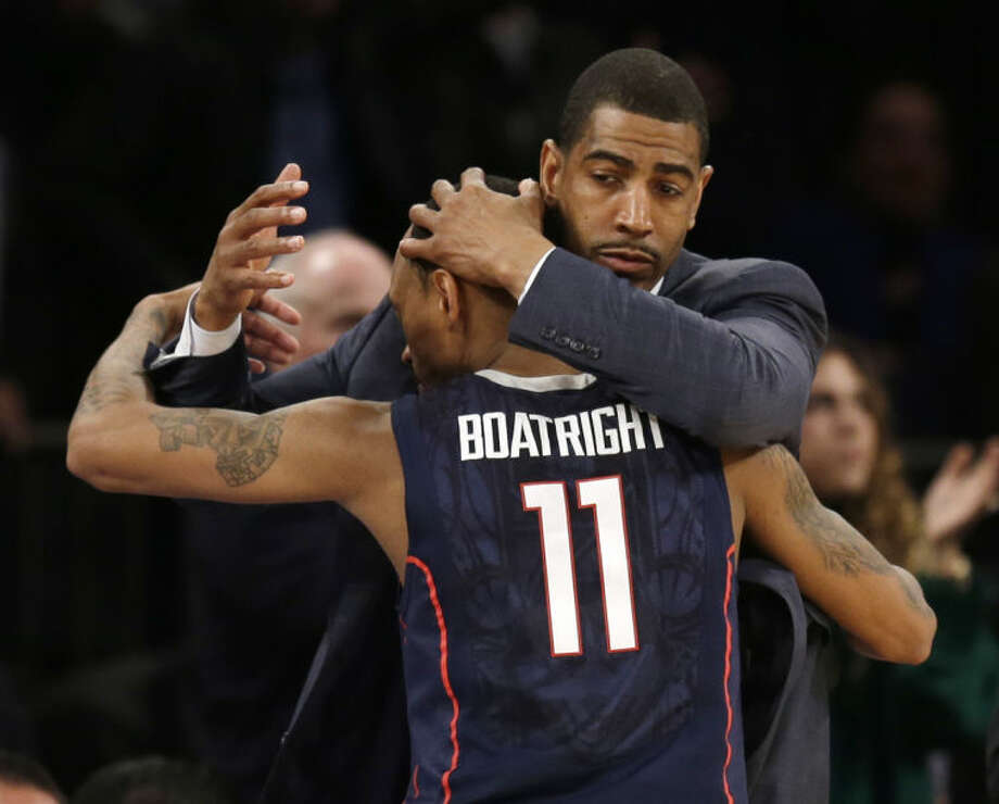 Connecticut coach Kevin Ollie hugs Ryan Boatright during the second half of a regional semifinal against Iowa State in the NCAA men's college basketball tournament Friday, March 28, 2014, in New York. Connecticut won 81-76. (AP Photo/Seth Wenig)