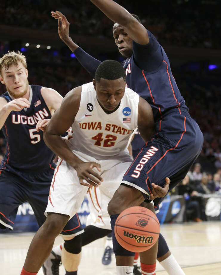 Iowa State's Daniel Edozie, center, loses the ball while covered by Connecticut's Niels Giffey, left, and Amida Brimah during the first half in a regional semifinal at the NCAA college basketball tournament Friday, March 28, 2014, in New York. (AP Photo/Frank Franklin II)