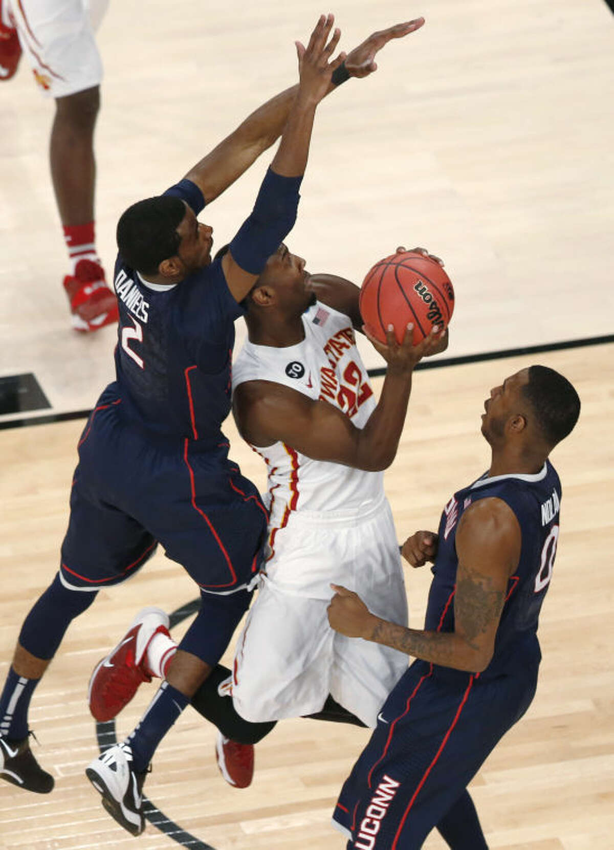 Iowa State's Dustin Hogue goes up between Connecticut's DeAndre Daniels, left, and Phillip Nolan during the first half in a regional semifinal of the NCAA men's college basketball tournament Friday, March 28, 2014, in New York. (AP Photo/Julio Cortez)
