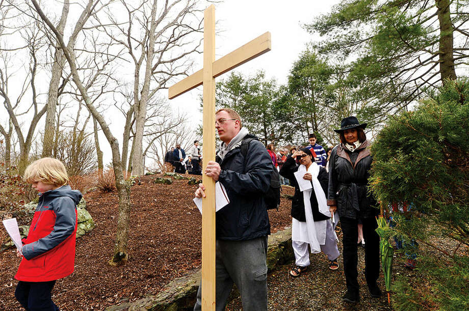 Hour photo / Erik Trautmann Michael Moon bears the cross as Father Sunil Pereira of St. Matthew's Church in Norwalk leads his parishioners and guests through the Stations of the Cross for their annual observation of Good Friday.