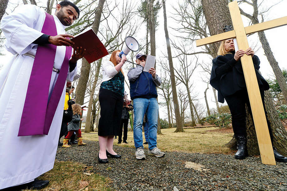 Hour photo / Erik Trautmann Pat Spinola reads the second station as Father Sunil Pereira of St. Matthew's Church in Norwalk leads his parishioners and guests through the Stations of the Cross for their annual observation of Good Friday.