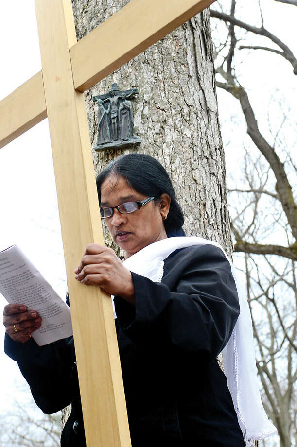 Hour photo / Erik Trautmann Regina David bears the cross as St. Matthew's Church in Norwalk parishioners and guests follow the Stations of the Cross for their annual observation of Good Friday.
