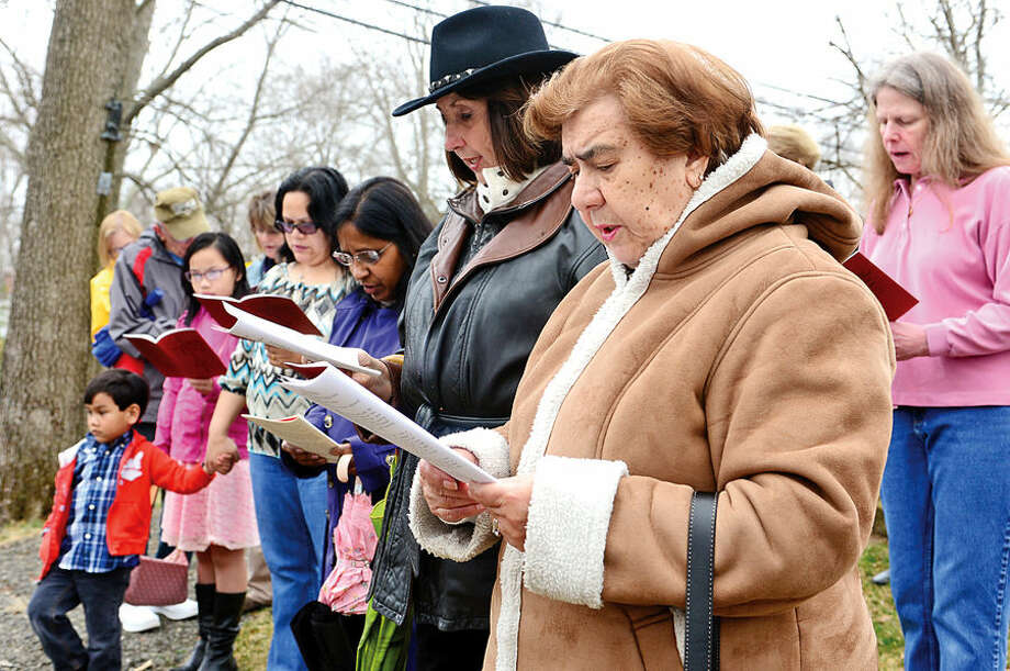 Hour photo / Erik Trautmann Regina DeCostanzo and other parishioners and guests of St. Matthew's Church in Norwalk follow the Stations of the Cross for their annual observation of Good Friday.