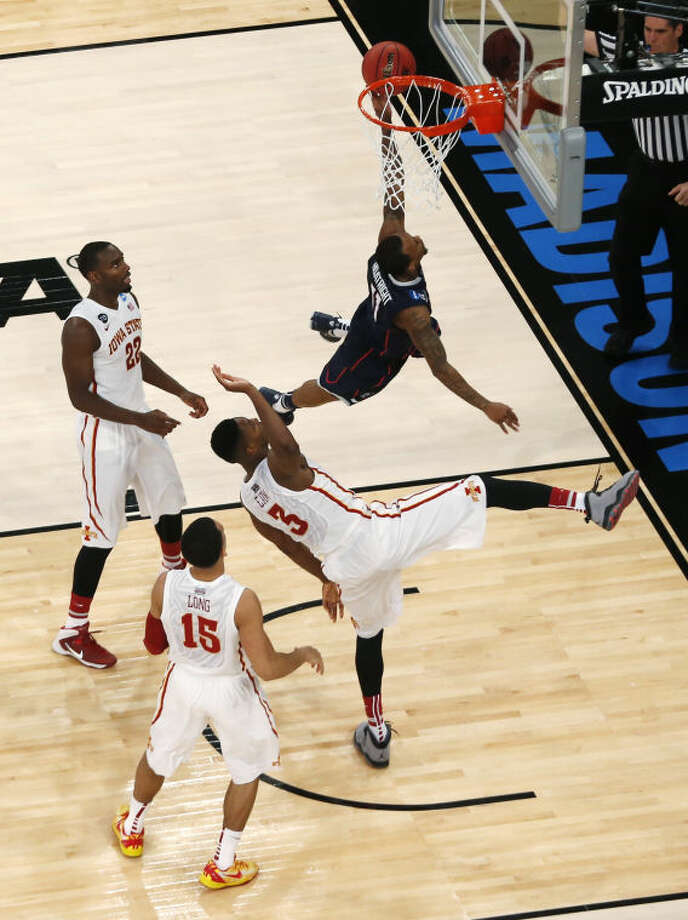 Connecticut's Ryan Boatright goes to the basket past, left to right, Iowa State's Dustin Hogue, Naz Long, and Melvin Ejim during the second half in a regional semifinal of the NCAA men's college basketball tournament Friday, March 28, 2014, in New York. (AP Photo/Julio Cortez)