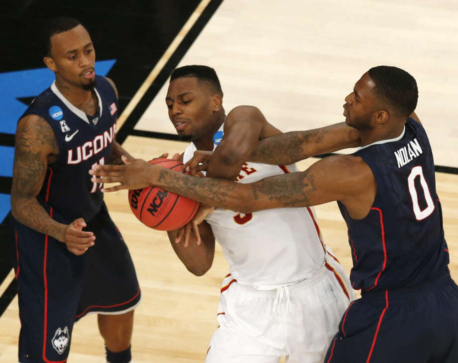 Iowa State's Melvin Ejim, center, struggles with Connecticut's Phillip Nolan, right, for the ball, with Connecticut's Ryan Boatright nearby during the second half in a regional semifinal at the NCAA men's college basketball tournament Friday, March 28, 2014 in New York. (AP Photo/Julio Cortez)