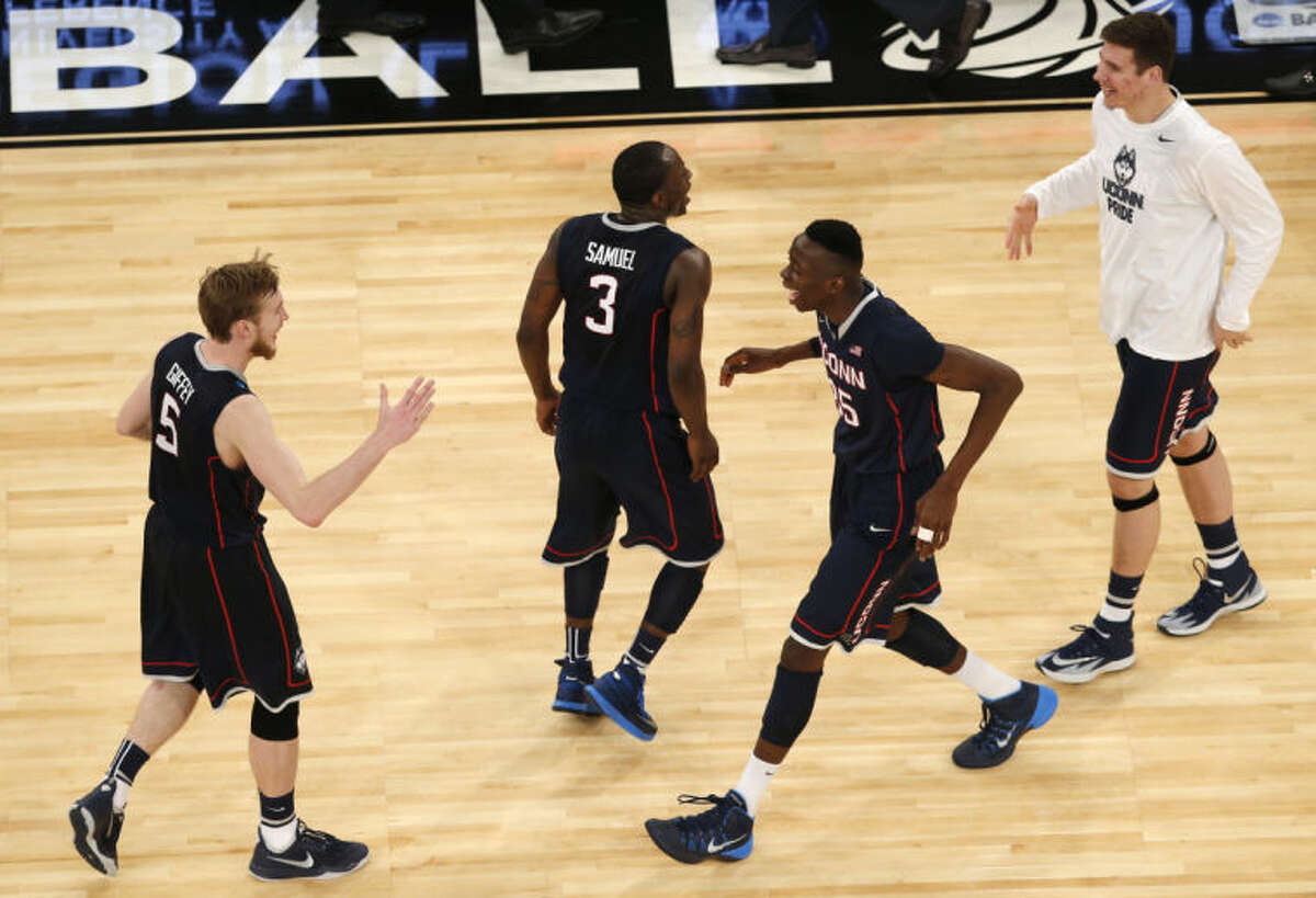 Connecticut players, left to right, Niels Giffey, Terrence Samuel, Amida Brimah, and Tyler Olander celebrate after after Connecticut defeated Iowa State 81-76 in a regional semifinal of the NCAA men's college basketball tournament Friday, March 28, 2014, in New York. (AP Photo/Julio Cortez)