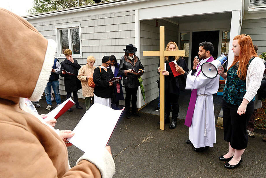 Hour photo / Erik Trautmann Father Sunil Pereira of St. Matthew's Church in Norwalk leads his parishioners and guests through the Stations of the Cross for their annual observation of Good Friday.