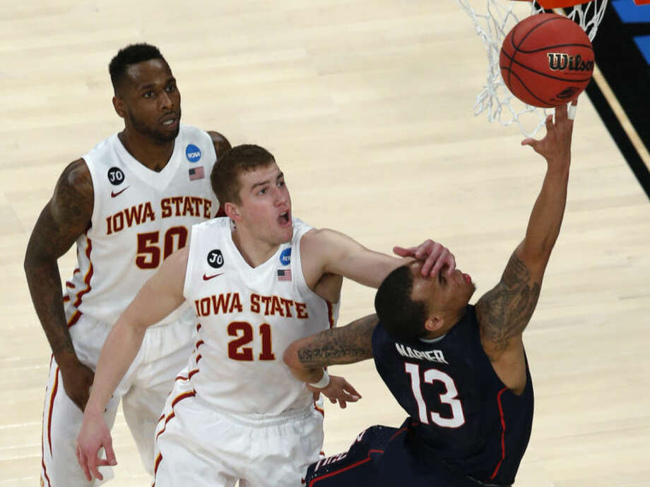 Connecticut's Shabazz Napier, right, is hit on the face by Iowa State's Matt Thomas while shooting during the second half in a regional semifinal of the NCAA men's college basketball tournament Friday, March 28, 2014, in New York. Iowa State's DeAndre Kane is at rear. (AP Photo/Julio Cortez)