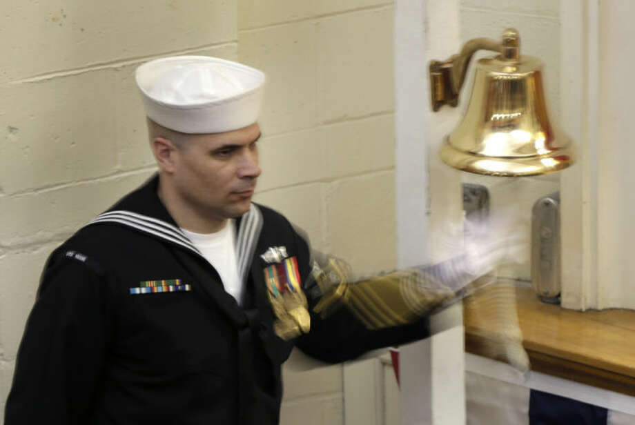 "A sailor rings a bell at the conclusion of the decommissioning ceremony for the fire-damaged USS Miami nuclear submarine at Portsmouth Naval Shipyard, Friday, March 28, 2014, in Kittery, Maine. Rear Adm. Ken Perry, commander of the submarine Group Two in Groton, Conn., where the sub was based, acknowledged the seriousness of the event, but told the crowd they were there to celebrate the submarine and its crew's achievements. ""This is a tribute. This is a celebration of the ship's performance and the superb contributions to the nation's defense and this is how we're going to treat it. So I expect to see some smiles out there,"" he said. (AP Photo/Robert F. Bukaty)"