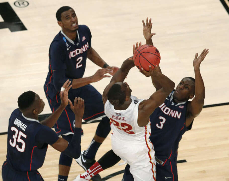 Iowa State's Dustin Hogue goes up for a shot as Connecticut's Amida Brimah, left, DeAndre Daniels, center, and Terrence Samuel defend during the first half in a regional semifinal of the NCAA men's college basketball tournament Friday, March 28, 2014, in New York. (AP Photo/Julio Cortez)