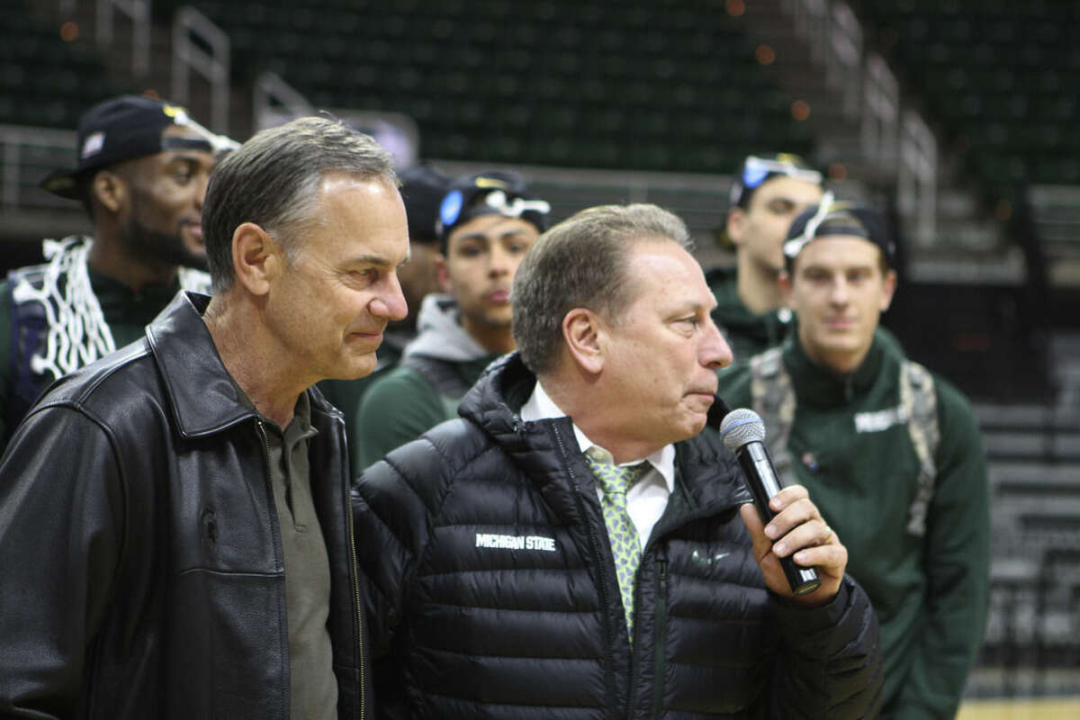 FILE - In this March 29, 2015, file photo, Michigan State basketball coach Tom Izzo speaks next to football coach Mark Dantonio in East Lansing, Mich., during a celebration of the team's win over Louisville in the NCAA men's college basketball tournament regional final in Syracuse, N.Y. It's no surprise that Tom Izzo is so invested not just in his Michigan State basketball team, but Mark Dantonio's football program as well. Izzo has always been fascinated by the gridiron, and that's impacted the way he's coached the Spartans on the hardwood. (AP Photo/The Citizen Patriot, Emily Lawler, File)