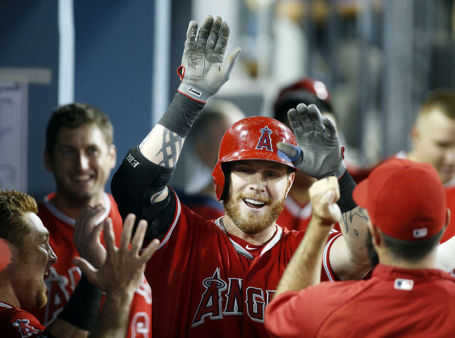 FILE - In this Aug. 4, 2014, file photo, Los Angeles Angels' Josh Hamilton celebrates his solo home run against the Los Angeles Dodgers with teammates in the dugout during the sixth inning of a baseball game in Los Angeles. An arbitrator has ruled Josh Hamilton will not be disciplined by Major League Baseball for violating his treatment program. MLB said Friday, April 3, 2015, it disagreed with the decision. (AP Photo/Danny Moloshok, File)