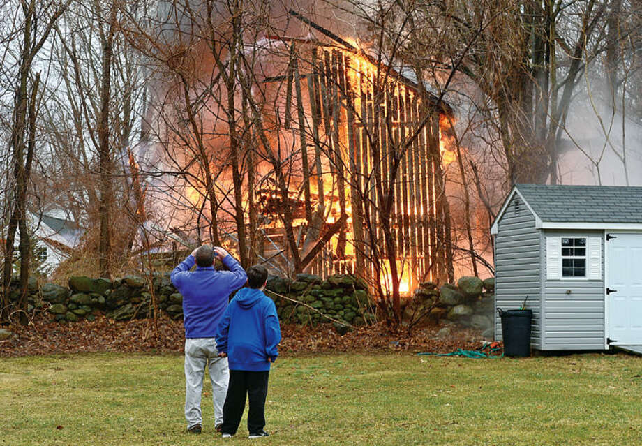 Hour photo / Erik Trautmann Jerry Quinn and his son Connor watch as a barn at 44 Fox Run Rd in Norwalk is destroyed by fire Saturday afternoon.