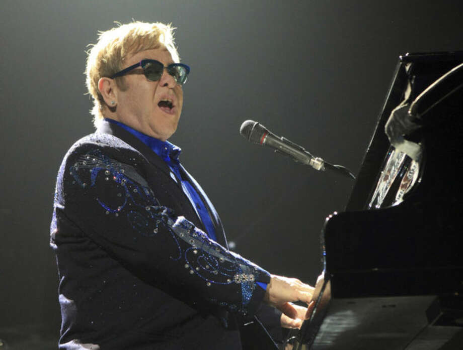 "FILE - This Nov. 14, 2013 file photo shows Elton John performing in concert during his Diving Board Tour 2013 at the Verizon Center in Washington D.C. Elton John released the 40th anniversary edition of his 1973 album, ""Goodbye Yellow Brick Road,"" on his 67th birthday. The album features remakes from contemporary acts like Ed Sheeran, Miguel, Zac Brown Band, Emeli Sande and others. (Photo by Owen Sweeney/Invision/AP)"