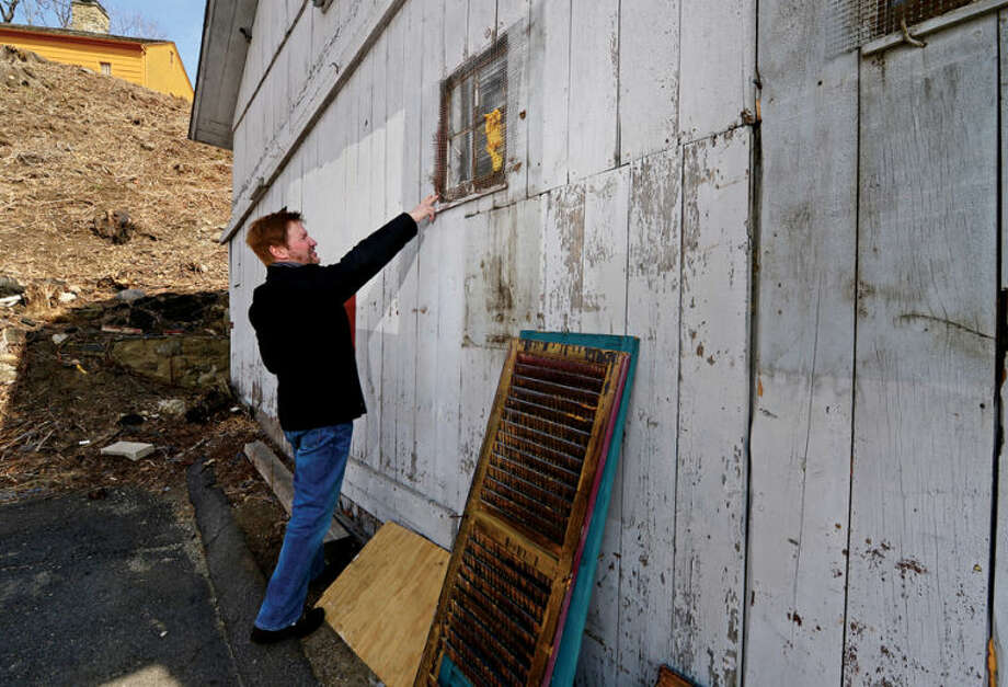 Hour photo / Erik Trautmann David G. Westmoreland of the Norwalk Historical Society and the Norwalk Historical Commission are begining restoration of fire-damaged Smith Street Jailhouse and nearby historic barn.